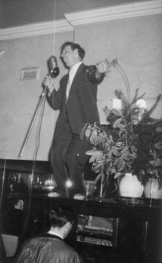 Old photo of man standing on piano and singing